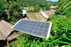 mini grid solar panel in jungle treetops and roofs