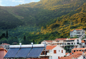 solar water heaters on orange tile roof of house against background of a mountain landscape in Montenegro