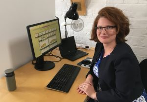 lady with glasses sitting in front of a PC at at desk