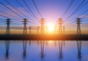 several electricity pylons, 5 in the foreground, with a sunset behind them and reflections in a lake beneath.