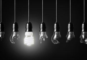 idea concept with broken bulbs and one glowing energy saving bulb
