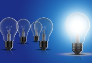 one illuminated light bulb with 4 others to the side unlit, against a blue background