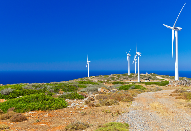 wind turbines on a rocky putlook overlooking the sea
