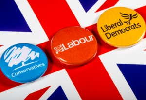 Union jack flag with 3 badges for the Tory, Labour and Lib dem parties.