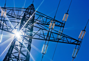 looking up at the top of an electricity pylon, with blue sky behind and a flash of sun behind the pylon