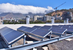 rows of solar panels against a backdrop of Cape Town, with cloud over Table Mountain