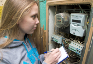 young lady with blonde hair, taking a meter reading