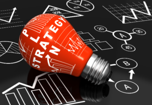 red light bulb with text reading 'strategy plan' - against a black & white graphic background