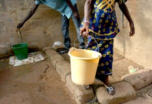 man and woman filling buckets with water from a standpipe in Africa