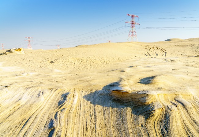 Middle Eastern desert, with electricity power lines on the horizon against a blue sky