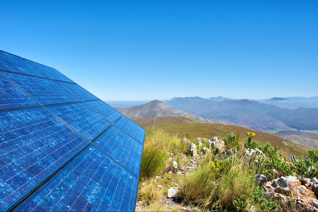 Solar panel in mountains with sky rocks and flowers