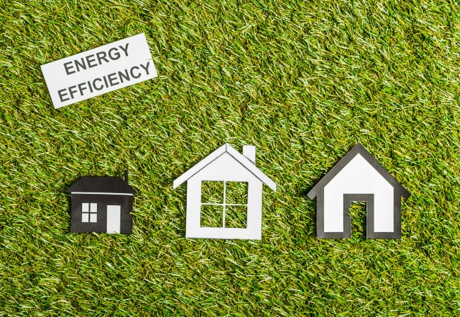 Grass background with 3 cut-outs of houses illustrating energy efficiency types